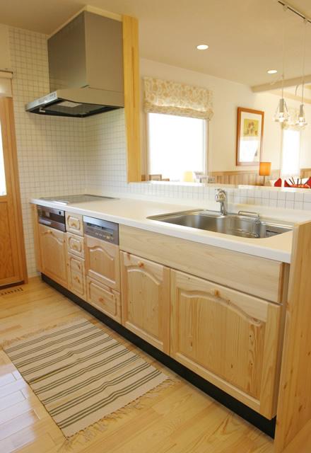 天然オーク材の無垢材を使用した風格あるシステムキッチン。設備部分は日本製を採用することでメンテナンスも安心。